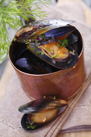 Steamed gourmet marine mussels in a copper pot seasoned with fresh dill for a delicious seafood appetizer photo