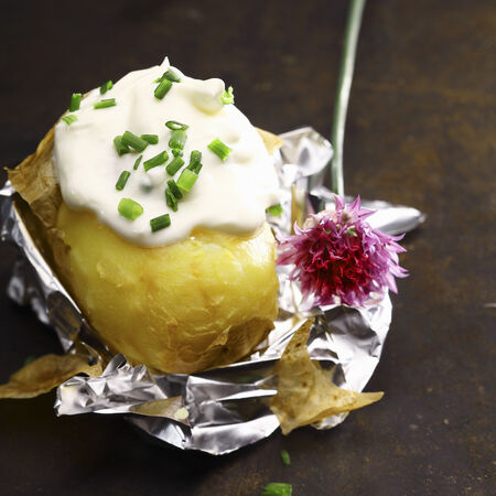 peeled off: Foil baked potato with sour cream and chopped fresh chives with a flower off a chive plant served partially peeled on its foil wrapper