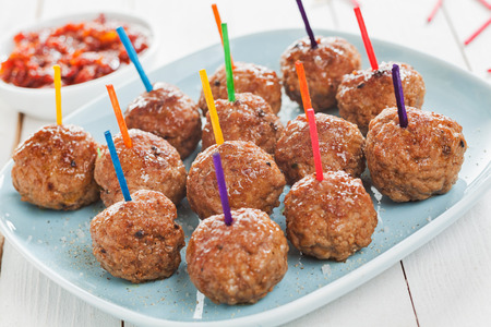 plateful: Buffet display of tasty spicy meatballs with colorful toothpicks for dipping arranged on a plate Stock Photo