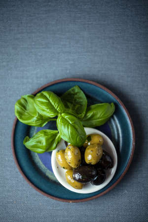 potherb: Overhead view of a bunch of fresh basil leaves with a bowl of black and green cured olives on a grey weave textile background with copyspace