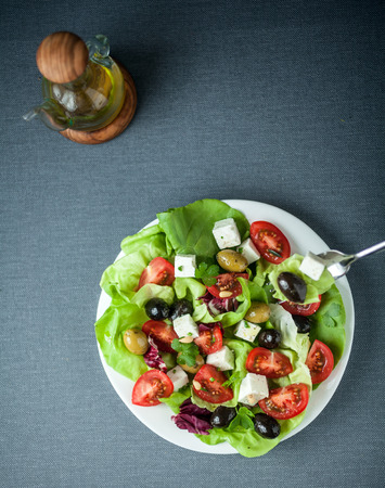 greek salad: Delicious fresh Mediterranean or Greek salad with lettuce, feta cheese, tomato and assorted olives served with olive oil, overhead view