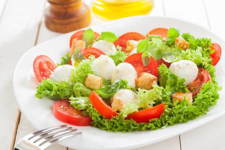 comidas saludables: Deliciosa ensalada de mozzarella italiana con picatostes de pan frito crujiente, rodajas de tomate hierbas frescas y lechuga con volantes servido en un plato sobre tablas de madera blanca