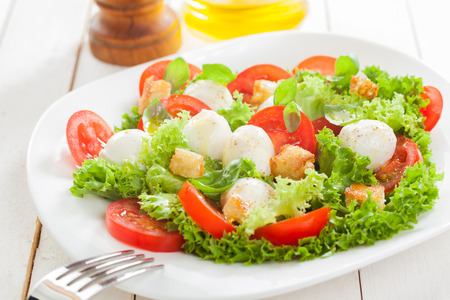 healthy meals: Delicious Italian mozzarella salad with crunchy fried bread croutons, sliced fresh tomato herbs and frilly lettuce served on a plate on white wooden boards Stock Photo