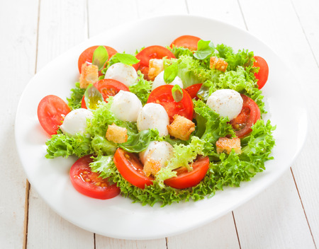 accompaniment: Fresh Italian salad with mozzarella cheese pearls on a bed of frilly lettuce with tomatoes and friend crunchy bread croutons served on a plate on white boards