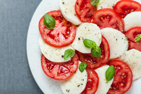 Colorful red and white Italian Caprese salad viewed from above with alternating slices of ripe red tomato and mozzarella cheese seasoned with fresh basil