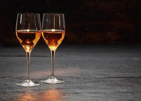 Pair of half-full half-empty wine glasses on stone surface