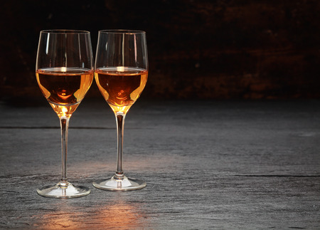 Pair of half-full half-empty wine glasses on stone surface