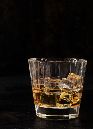 Iced bourbon or whiskey in a glass tumbler on a dark background with vertical copyspace photo