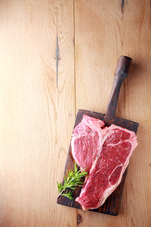 meat counter: Uncooked tender porterhouse or t-bone steak on an old wooden board with a sprig of fresh rosemary waiting to be cooked, view from above on wood with copyspace
