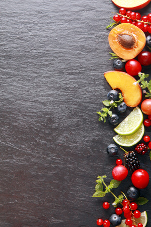 dark grey slate: Border of fresh fruit and herbs along the right of the frame with assorted berries, apricot, peach and lemon on a dark grey slate background with copyspace