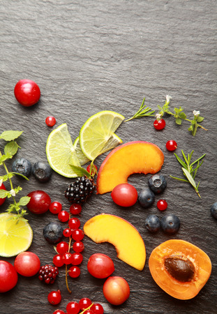 dark grey slate: Colorful healthy sliced fresh fruit , assorted berries and herbs on a textured dark grey slate background with copyspace, view from above