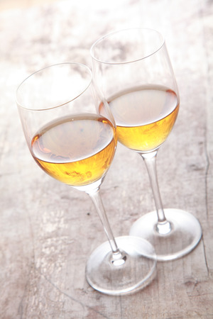 sherry: Two glasses of white sherry wine standing touching viewed high angle on a rustic wooden garden table in sunlight