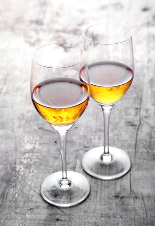 sherry: Romantic lunch for two in the garden with a pair of wineglasses with white wine standing with their bowls touching on a rustic wooden outdoor table in sunlight