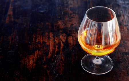 Glowing cognac or brandy in an elegant snifter glass on an old dark wooden bar counter with copyspace, high angle view photo