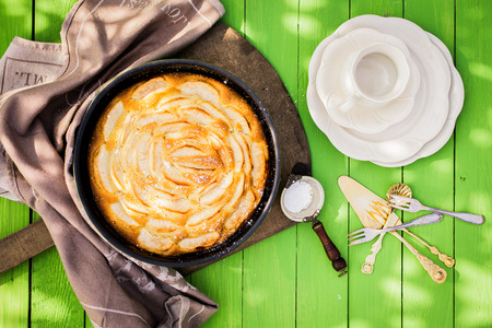 Coffee time in the garden with fresh apple pie with an overhead view of an empty cup and cake plates alongside a golden tart in a dish with a strainer of powdered sugar to sprinkle on top photo