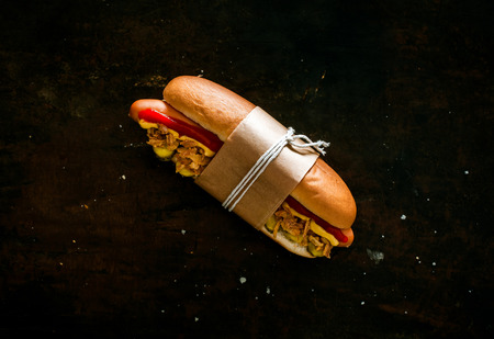 Takeaway hot dog with a smoked Wiener sausage and all the trimmings on a fresh bun tied with brown paper and string on a black background with copyspace