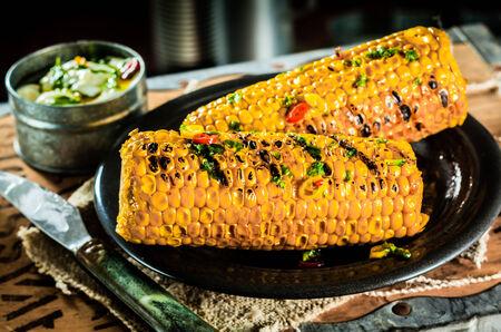 elote: La barbacoa sabrosa o maíz a la parrilla en la mazorca sazonado con especias y hierbas en una arpillera settingwith rústico en una vieja tapa de caja de té Foto de archivo