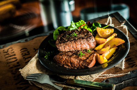 Healthy lean grilled medium-rare beef steak and vegetables with roasted pumpkin and a leafy green herb salad in a rustic pub or tavern