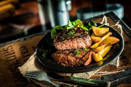 lunch: Saludable filete medio crudo a la parrilla carne de res magra y verduras con calabaza asada y ensalada de hierbas de hoja verde en un pub o taberna r�stica