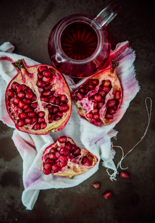 Making fresh pomegranate juice with an overhead view of a broken open fruit displaying the ripe red seeds on a stained muslin cloth with a jug of freshly prepared juice alongside photo