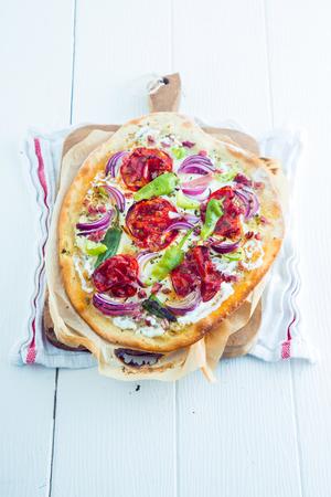 pancetta cubetti: Alsaziana tradizionale Tarte Flambee con una crosta di pasta sottile, lardelli o pancetta a cubetti, formaggio o creme fraiche, erbe, pomodori e cipolle su assi di legno bianco per la deliziosa cucina francese