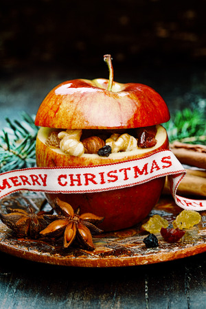 christamas: Macro Red Holiday Apple with Christmas Ribbon on Vintage Wooden Table. Stock Photo
