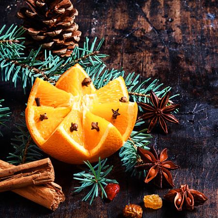Christmas fruit and spice background with a colorful pattern cut orange decorated with cloves nestling on pine foliage with a cone, cinnamon, star anise and nuts on a rustic backdrop in square format