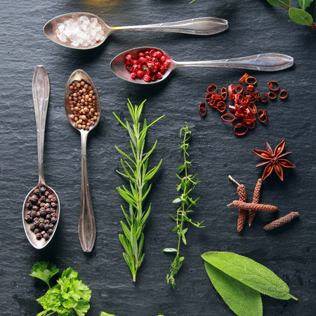 Display of fresh herbs and spices with assorted peppercorns in spoons, star anise and cayenne pepper, fresh parsley, rosemary oregano and bay leaves, overhead view photo