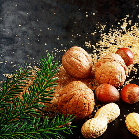 tree nuts: Fresh assorted whole nuts for a festive Xmas with almonds, hazelnuts and peanuts in their shells on brown caramelized sugar with pine foliage on a dark background with copyspace for your greeting