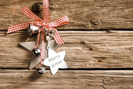 Rustic decorative Christmas background on weathered wooden boards with a pretty dainty red and white checked ribbon and bow decorated with stars and metal bells and a message - Merry Christmas photo