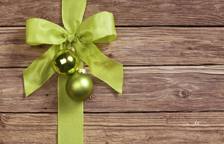 seasonal greeting: Decorative green bow decorated with two Christmas bauble ornaments on a wooden background with copyspace for your seasonal greeting Stock Photo