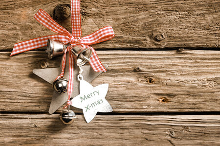 Celebrating a country Christmas with decorative stars and silver bells habging from a red and white checked ribbon and bow on rustic wooden boards with a star-shaped tag with the message - Merry X-mas
