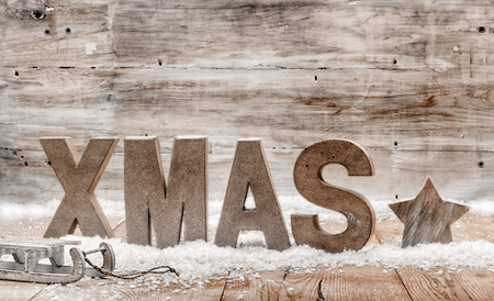 Wood craft rustic Christmas background with wooden letters spelling Xmas standing in snow with a star and small kids sleigh or toboggan against a weathered wooden wall with copyspace for your greeting photo