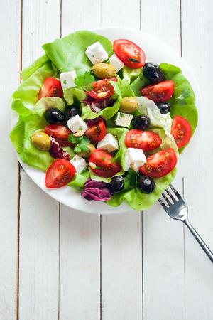 ensalada de tomate: Ensalada fresca y nutritiva con queso feta, tomate, verduras de hoja verde y aceitunas en un plato, vista aérea en blanco rústico pintado juntas con copyspace