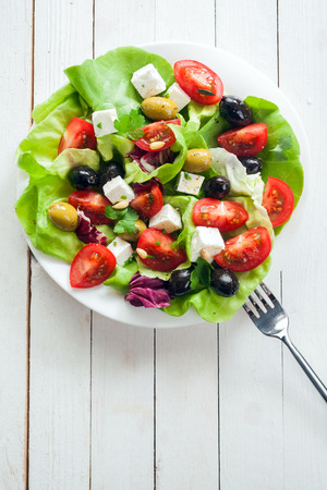 greek cuisine: Nutritious fresh salad with feta, tomato, leafy greens and olives on a plate, overhead view on rustic white painted boards with copyspace Stock Photo