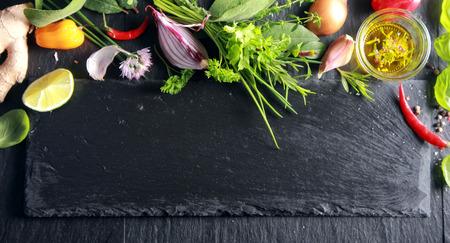新鮮な果物、野菜、経験豊かなオリーブ オイルと copyspace と暗いテクスチャ スレート背景にハーブの上部のボーダー