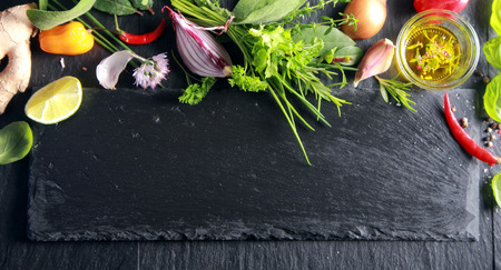 Upper border of fresh fruit, vegetables, seasoned olive oil and herbs on a dark textured slate background with copyspace Stock fotó
