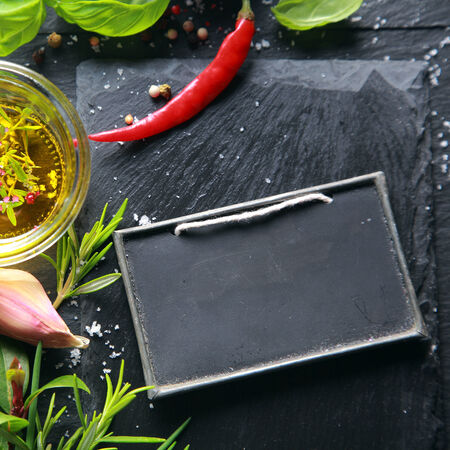 potherb: Fresh seasoning ingredients with asil, chili pepper, rosemary, garlic and seasoned olive oil with a blank slate with copyspace for your menu or text, view from above Stock Photo