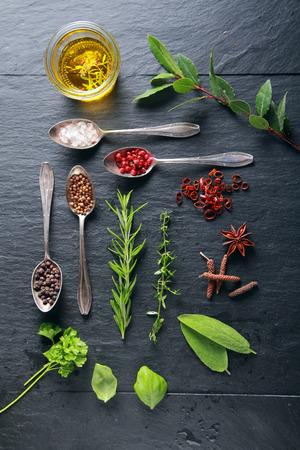 potherb: Elementos de comida y una cuchara en la tabla de madera Negro Foto de archivo