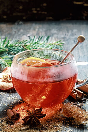 cinammon: Hot cup of spiced hot tea or gluhwein with a crystallized sugar stirrer and citrus fruit surrounded by dried cinammon , star anise and caramelised sugar on a rustic Christmas backdrop with copyspace