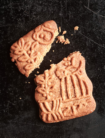 Traditional Dutch speculoos biscuit, a spicy crunchy shortcrust cookie for the feast of St Nicholas, now served to celebrate Christmas worldwide, broken and crumbled photo