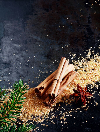 stick of cinnamon: Christmas background with traditional spices with a bundle of stick cinnamon and star anise on scattered caramelized brown sugar scattered on a dark surface with copyspace and decorated with pine