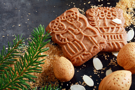 Spicy crunchy speculoos Christmas biscuits, a Dutch speciality confectionery originally baked for the feast of St Nicholas and decorated with religious patterns and pictures with almonds and fir twig