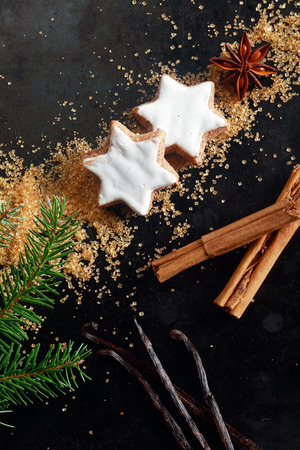 stick of cinnamon: Christmas food still life with copyspace for your seasonal greeting with an overhead view of glazed white star shaped cookies, vanilla pods, stick cinnamon and sugar on a dark background Stock Photo