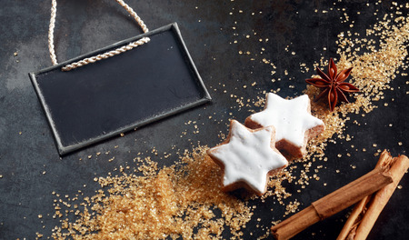 blank slate: Christmas baking background with glazed white spicy star shaped biscuits surrounded by ingredients - star anise, brown sugar and stick cinnamon with a blank slate with copyspace for a menu or recipe