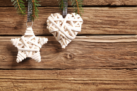 seasonal greeting: Two rustic straw Christmas ornaments on a textured wooden background with copyspace with a symbolic star and heart for a seasonal greeting for loved one