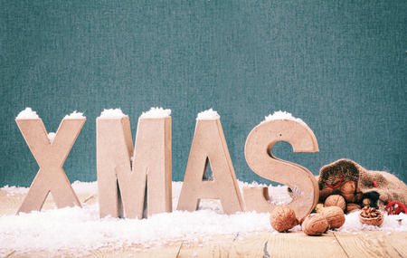 Cool winter Xmas background with white alphabet letters standing in white winter snow with walnuts in their shells spilling from a hessian bag against blue with copyspace for your Christmas greeting photo