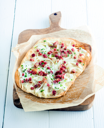Tarte Flambee, a traditional French tart from the Alasace region, with a thing pastry base, creme fraiche or cheese, lardons - cubed smoked bacon, onions and fresh herbs served on a wooden board