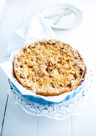 High key image of a delicious fresh baked plum pie on a decorative doily on white boards with plates ready to be served photo