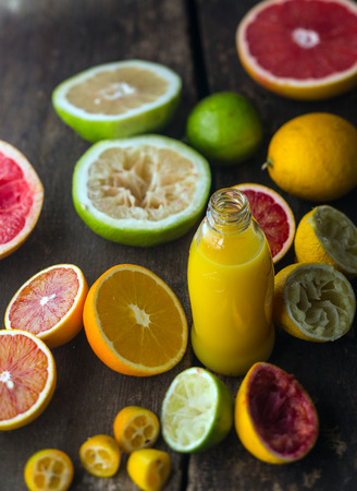 Preparing fresh citrus juice in a rustic kitchen with a bottle of orange juice blend surrounded by halved oranges, grapefruit, blood orange , lime and lemon, some of which have been squeezed photo